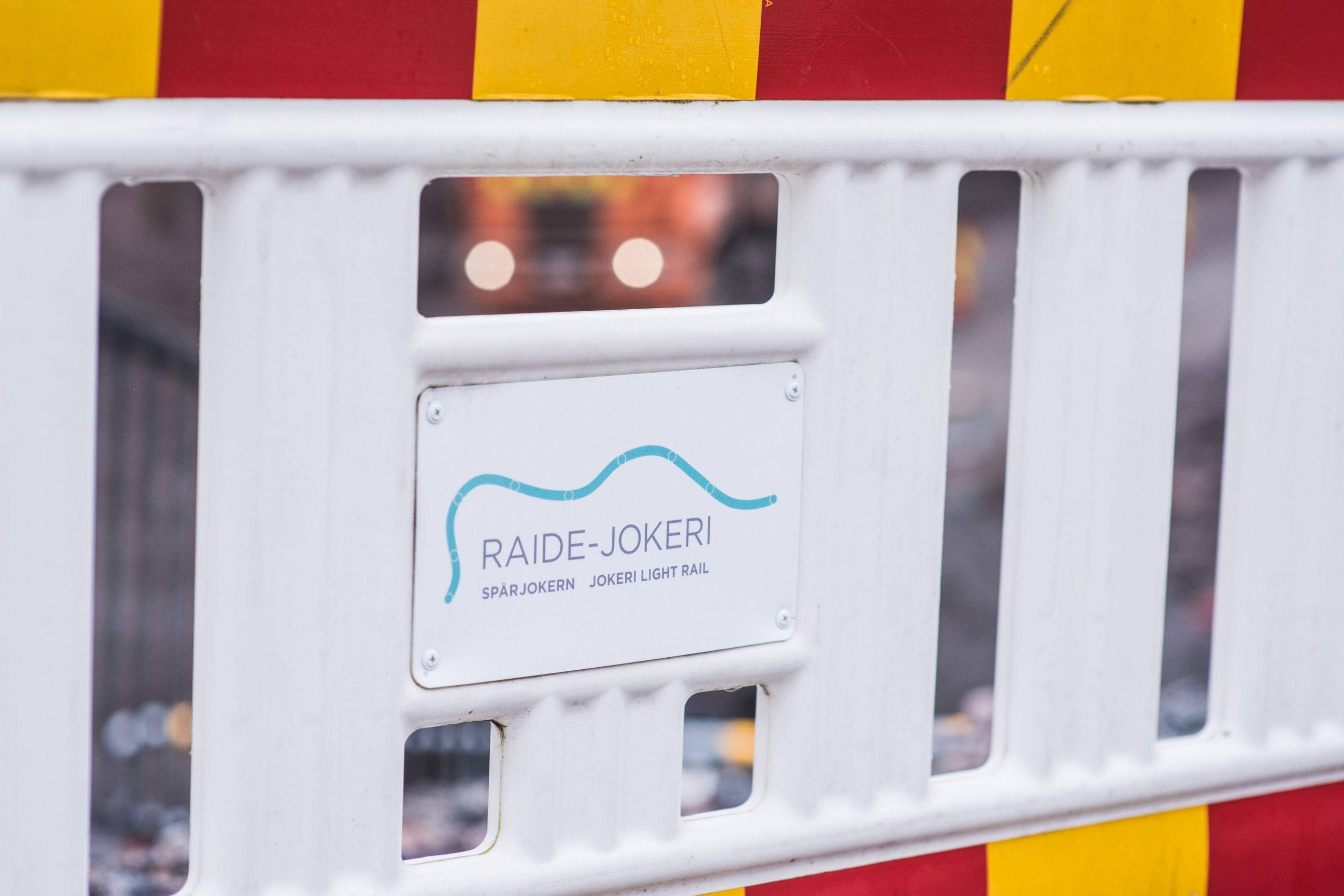 Kuva muovisesta työmaa-aidasta, jossa on Raide-Jokerin logo.