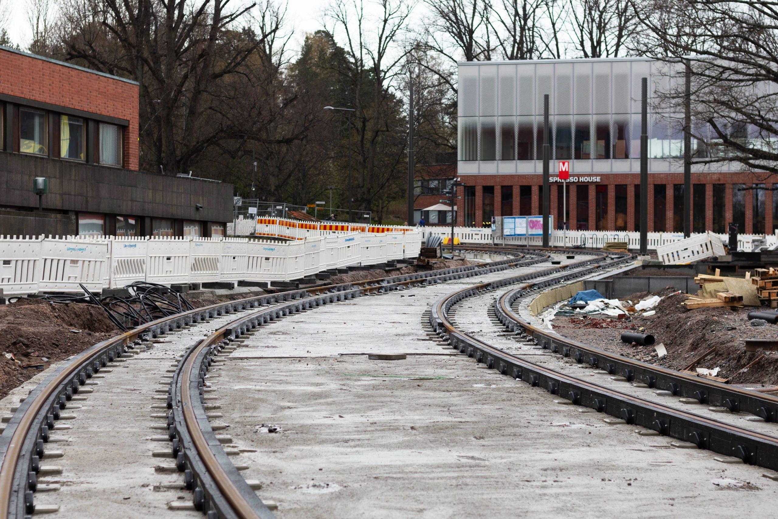 Korkeakoulunaukiolle asennetut kiskot ja valettu ratalaatta, taustalla näkyy Otaniemen metroaseman sisäänkäynti.