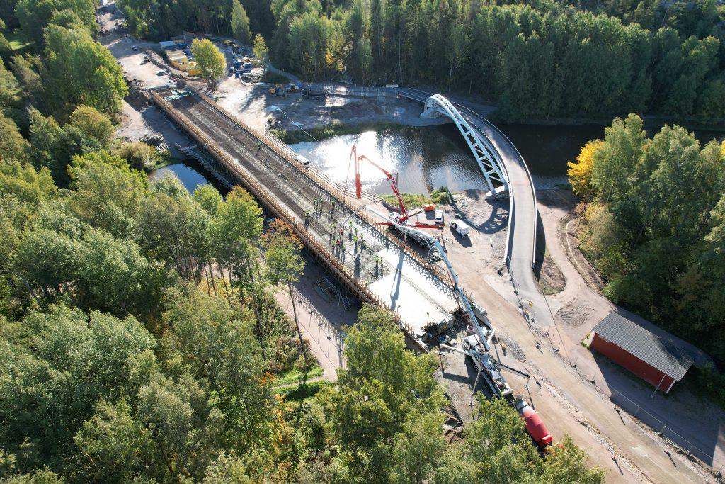 Ilmakuva Raide-Jokerin siltatyömaalta Vantaanjoelta. Työmiehet valavat sillan betonikantta.